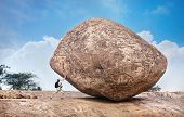 picture of tamil  - Man with backpack pushing a huge stone in Mamallapuram cave complex Tamil Nadu India - JPG