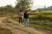 Couple Walking On Path At Countryside
