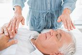 Senior man having Reiki treatment by massage therapist at spa