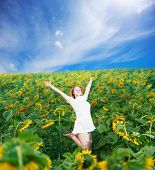 Beautiful young woman in white sundress jumps among sunflowers on flower field under blue cloudy sky