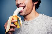 Smiling Young Man Eating A Banana
