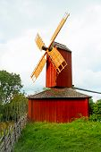 Red Windmill With Archaic Fence.