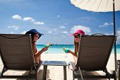 stock photo of panama hat  - Two ladies in hat sitting in chaise longue with glass of cocktail - JPG