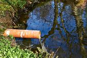 stock photo of scum  - Industrial Pipe Dumping Waste Water Into The river - JPG