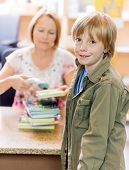 Portrait of young boy with librarian scanning books at checkout counter in library