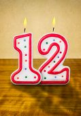 Burning birthday candles number 12 on a wooden background