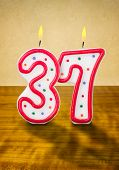 Burning birthday candles number 37 on a wooden background