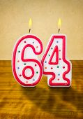 Burning birthday candles number 64 on a wooden background