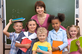 image of school child  - Line of smart classmates looking at camera with happy teacher behind them - JPG