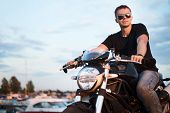 Romantic portrait handsome biker man sits on a bike