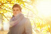 Handsome guy backlighting portrait with bokeh, outdoor in autumn park.