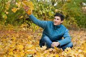 Cool happy guy siiting on autumn foliage in park.