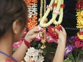 Closeup rear view of a woman looking at artificial flowers necklaces
