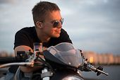 Romantic portrait handsome biker man in sun glasses sits on a bike on a sunset near lake and city