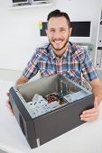 Computer engineer smiling at camera beside open console in his office