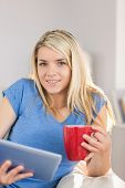 Relaxed beautiful young woman using digital tablet while drinking coffee in the living room at home