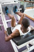 High angle view of male weightlifter doing leg presses in gym