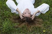 Beautiful girl in white dress lying down at grass