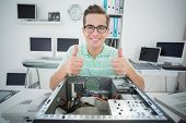Smiling technician working on broken computer showing thumbs up in his office