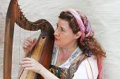 MUSKOGEE, OK - MAY 24: Woman dressed in vintage clothes plays harp at the Oklahoma 19th annual Renai
