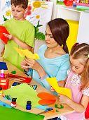 Happy children  with teacher at classroom.