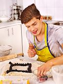 Young man  baking cookies in oven.