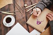 Image of cup of coffee and objects for hand drawing and artist hands drawing man in notepad