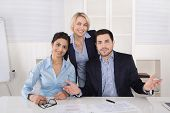 Portrait: Successful Smiling Business Team Of Three People; Man And Woman In The Office.