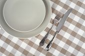 Grey empty plate with vintage fork and knife on beige checkered tablecloth.