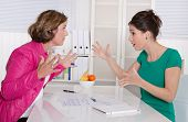 Two Business Woman Disputing In The Office Having Disagreement.