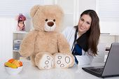 Young Female Doctor For Children With A Teddy Bear.
