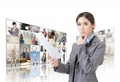 Confident Asian business woman holding paper and standing in front of TV screen wall, closeup portra