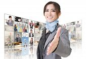 Confident Asian business woman want to shake hand with you and standing in front of TV screen wall,