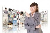 Confident Asian business woman point at the screen and standing in front of TV screen wall, closeup