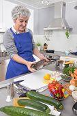 Happy Senior Woman In The Kitchen Preparing Fresh Fish.
