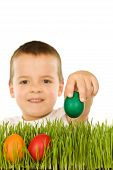 Boy setzen colorful Easter Eier im Gras