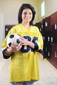 A beautiful teen girl in an oversized jersey, clutching a soccer ball in a locker room.