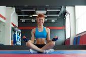 Smiling athlete posing sitting in lotus position