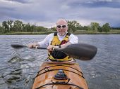 a bow view of a senior male paddling a home-built wooden sea kayak on a lake in Colorado, focus on face with arms and paddle in a motion blur