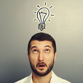 surprised young man looking up at drawing light bulb over grey background
