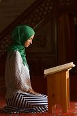 stock photo of quran  - Young muslim woman reading Quran in turkish mosque - JPG