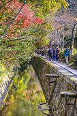 KYOTO, JAPAN - NOVEMBER 19, 2014: Tourists observe fall colors along Philosopher's Path in Kyoto. The route is named for  Nishida Kitaro, a renown Kyoto University Philosopher who used the path daily.