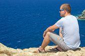 Man Sitting On Rocky Cliff On Sea Coast