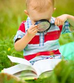Little boy is reading book using magnifier while sitting on green grass outdoors