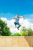 Active Sporty Lifestyle. Athletic Jumping Man. Blue Sky Background.