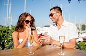 love, dating, people and holidays concept - smiling couple wearing sunglasses with champagne and sma
