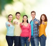 friendship, ecology, gesture and people concept - group of smiling teenagers pointing finger on you