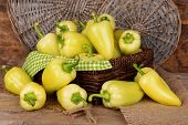 Yellow peppers in basket on wicker background