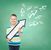 advertising, direction, education and childhood concept - smiling little boy with white blank arrow