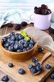Wooden bowl of blueberries and metal mug of blackberries on cutting board on sacking napkin on woode
